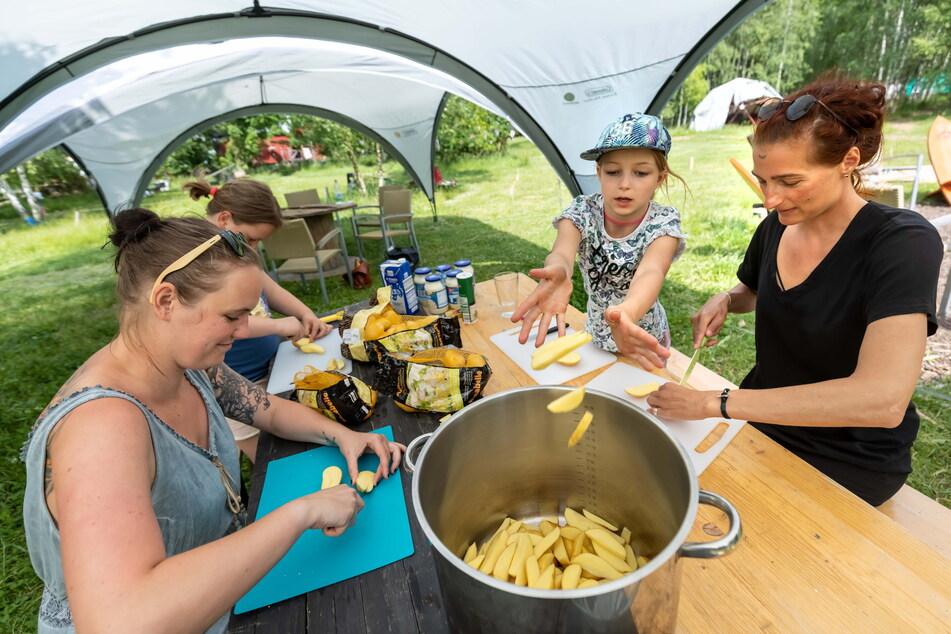 Abends wird zusammen gegessen, vorher helfen alle mit. Denise Winkler (35 v.l.), Amelie (9), Nele (9) und Karina Falke (44) schnippeln gemeinsam.