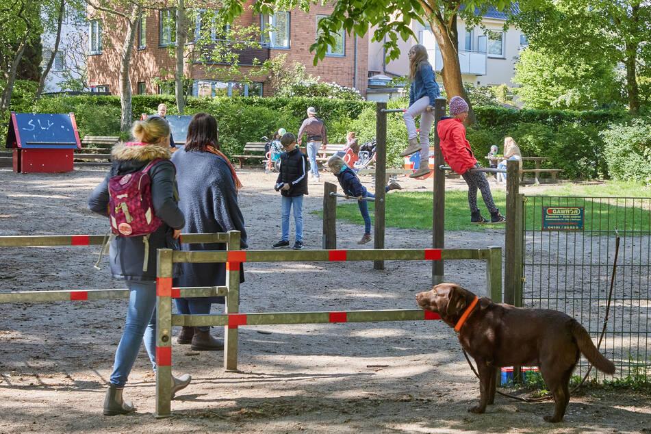 Kinder und Erwachsene besuchen einen Spielplatz in Hamburg-Lokstedt.
