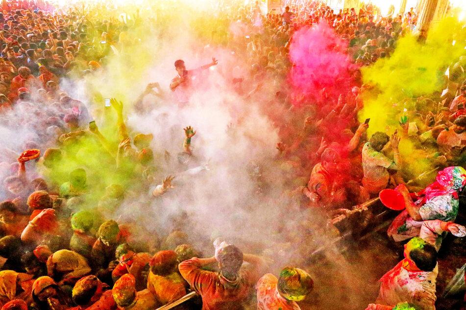 Anhänger werfen während des Holi-Festes im Govind Dev Ji-Tempel in Jaipur in Indien mit buntem Farbpulver.