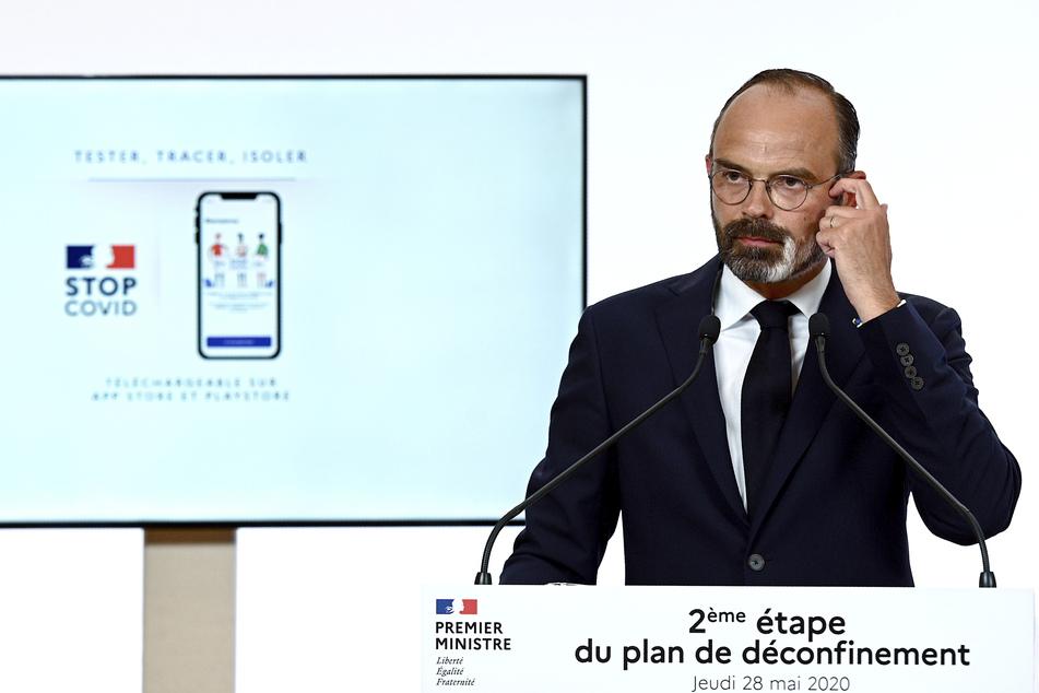 """Edouard Philippe (49), Premierminister von Frankreich, äußert sich neben einem Bildschirm, auf dem die """"StopCovid""""-App gezeigt wird."""