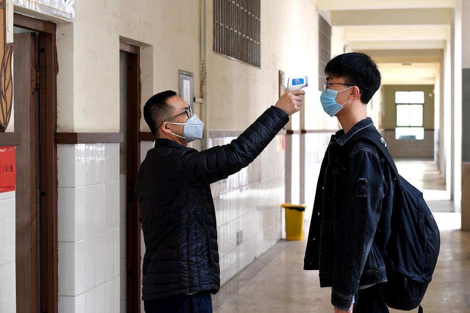 Ein Lehrer misst die Temperatur bei einem Schüler in der Schule Nr. 9 in Zhengzhou (China). Soweit soll es hierzulande jedoch nicht kommen.