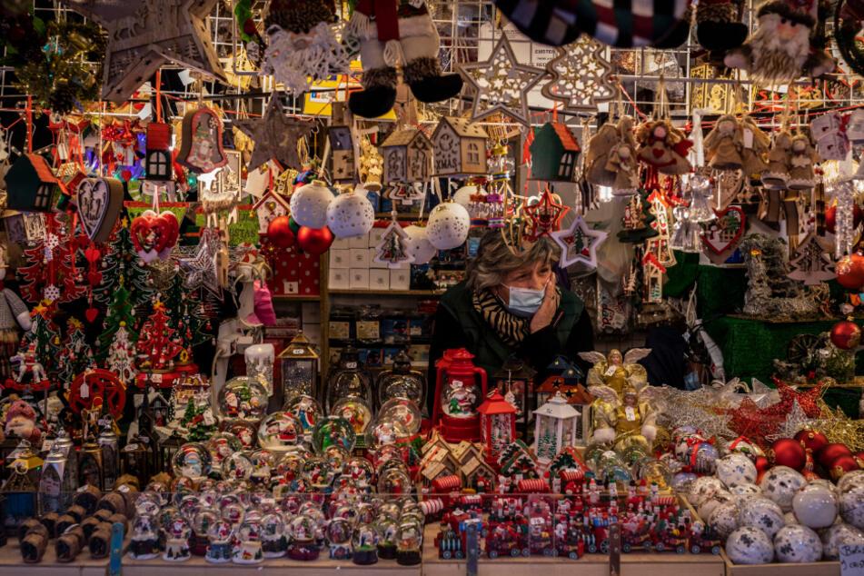 Eine Verkäuferin mit Maske wartet auf Kunden an einem Weihnachtsmarktstand auf der Plaza Mayor.