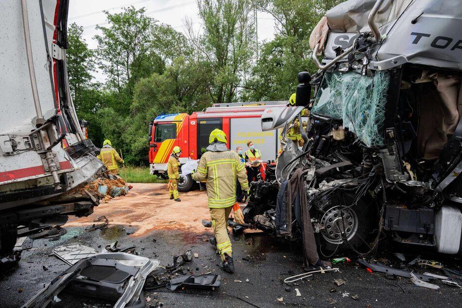 Einsatzkräfte der Feuerwehr stehen an einem LKW-Wrack auf der Autobahn A2 am Autobahnkreuz Hannover-Buchholz.