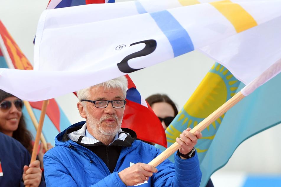 Franz Steinle, Präsident des Deutschen Skiverbandes (DSV), schwenkt die Flagge des internationalen Skiverbandes (FIS), die er zuvor vom Österreichischen Skiverband überreicht bekam. Oberstdorf in Deutschland wird 2021 Ausrichter der 53. Nordischen Skiweltmeisterschaften sein.