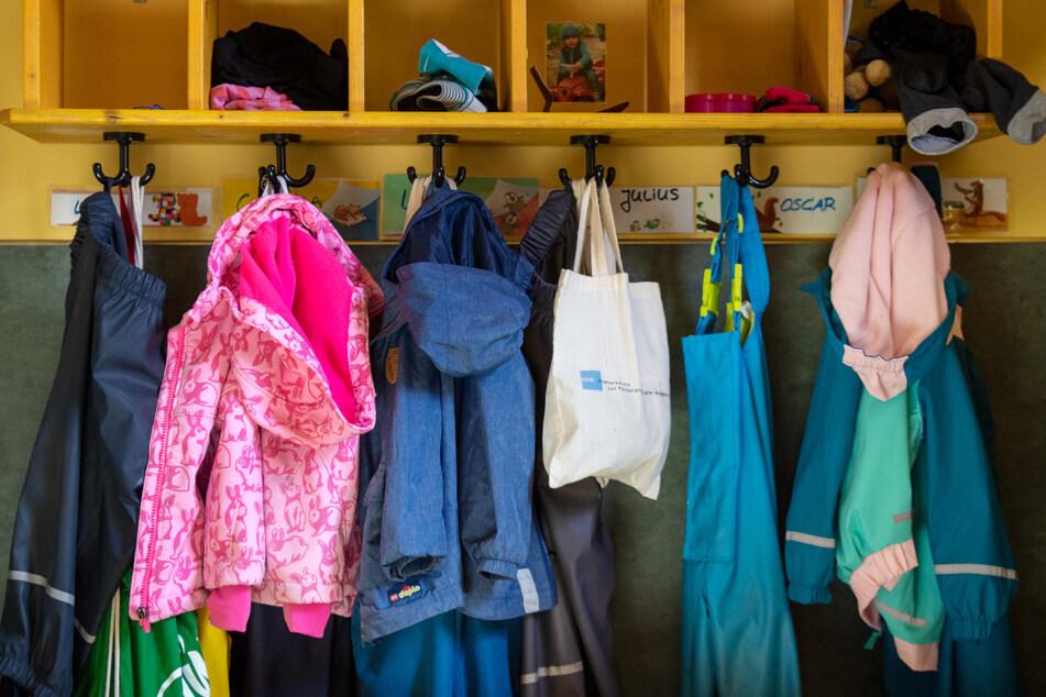 Jacken und Taschen hängen im Eingangsbereich in einem Kindergarten. Ab Montag wird es in den Kitas wieder etwas voller.