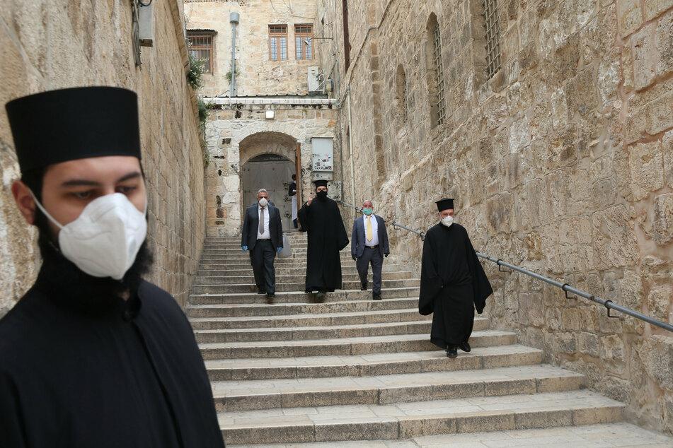 Orthodoxe christliche Geistliche mit Mundschutz gehen am orthodoxen Karfreitag in der Nähe der Grabeskirche durch die Jerusalemer Altstadt. (Archivbild)