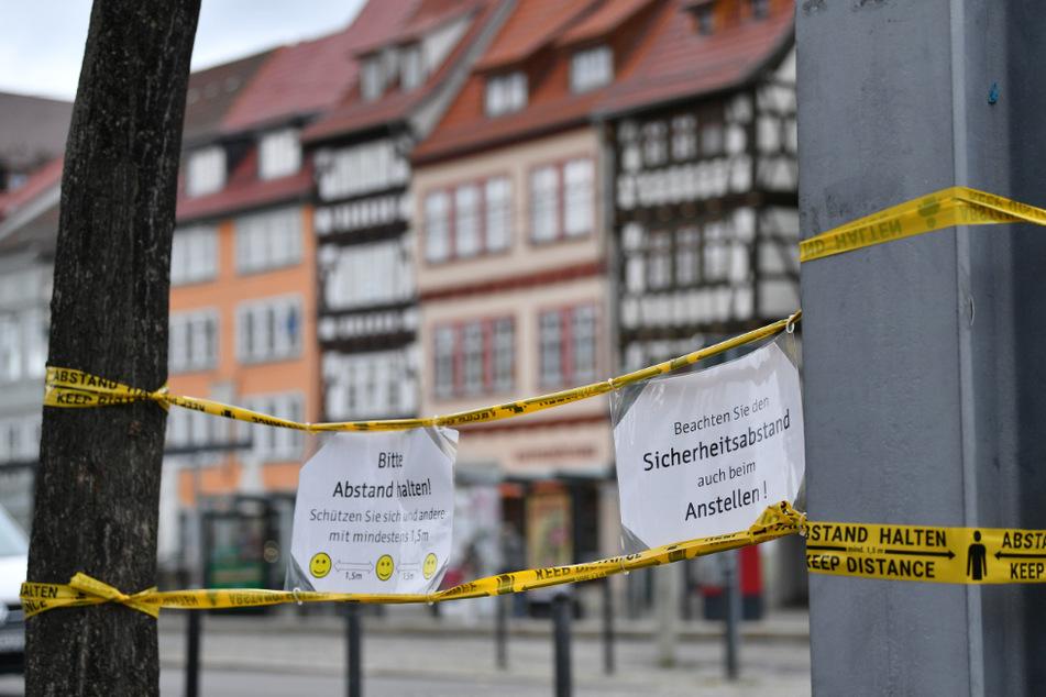 """Zettel mit den Hinweisen """"Bitte Abstand halten!"""" und """"Beachten Sie den Sicherheitsabstand auch beim Anstellen!"""" sind mit Klebeband behelfsmäßig am Domplatz in Erfurt angebracht. (Symbolfoto)"""
