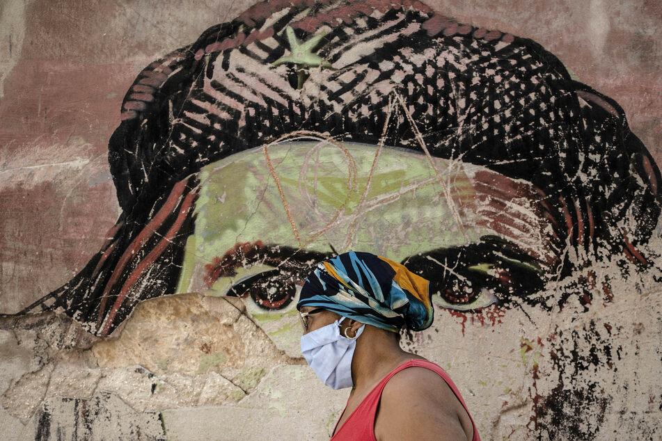 """Eine Frau mit Maske geht in Havanna inmitten der Corona-Pandemie an einem verfallenen Wandgemälde vorbei, das den in Argentinien geborenen kubanischen Revolutionshelden Ernesto """"Che"""" Guevara darstellt."""
