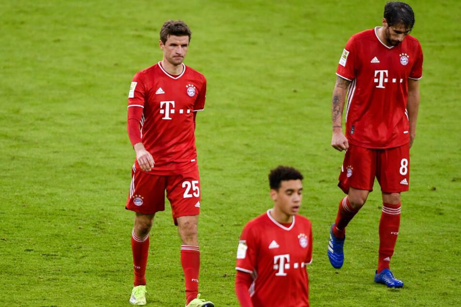 Thomas Müller (l-r), Jamal Musiala und Javi Martinez gehen sichtlich unzufrieden in der Halbzeit Richtung Kabinen.