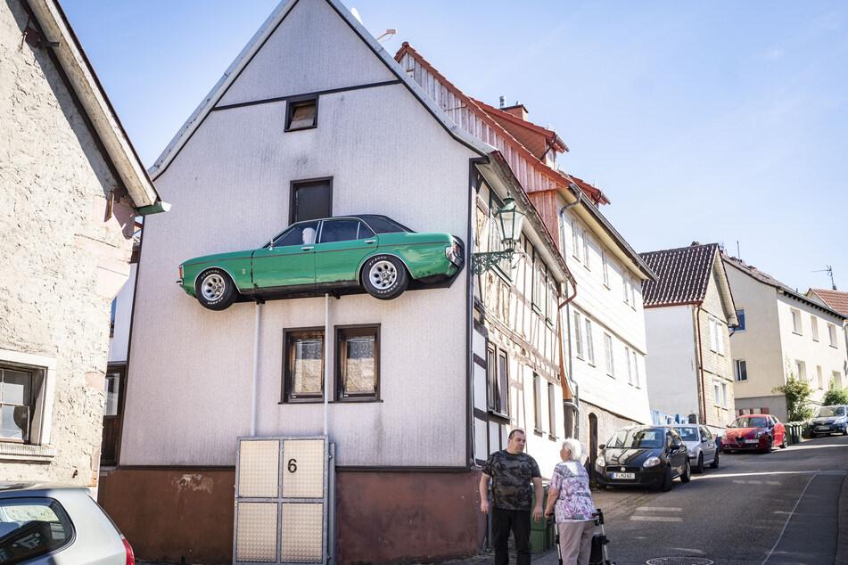 Matthias Hoffmann (u.) steht vor seinem Haus, an dessen Fassade er die linke Seite eines alten, längs aufgeschnittenen Ford Granada auf zwei Stützen angebracht hat.