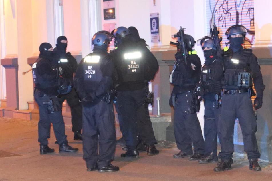 Schwer bewaffnete Polizisten sichern die Umgebung.