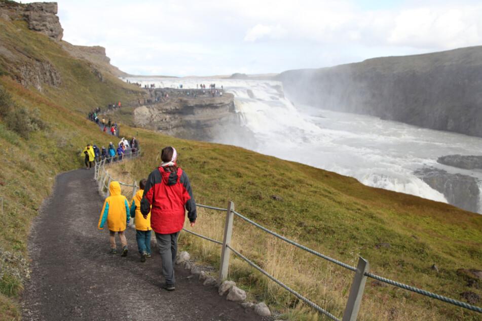 Island, Geysir: Touristen wandern zum isländischen Wasserfall Gullfoss.