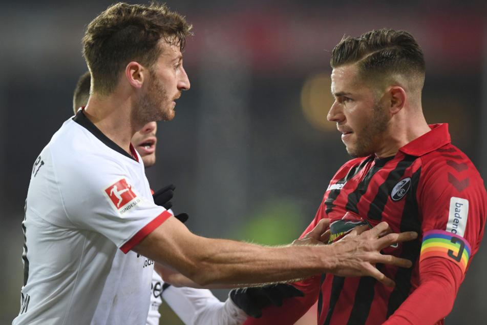 David Abraham (l) von Frankfurt und Christian Günter (r) von Freiburg geraten nach einem Foul an Trainer Streich von Freiburg aneinander.