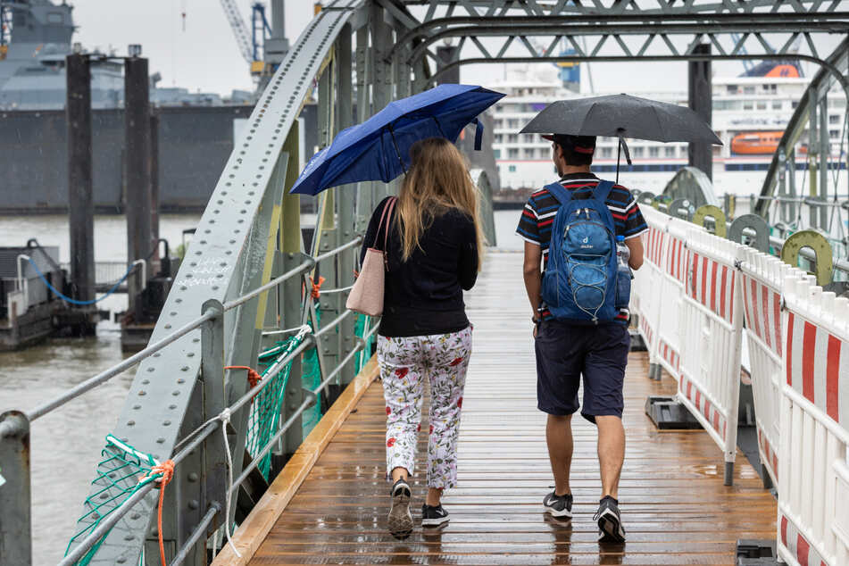 Mit Regenschirmen schützen sich eine Frau und ein Mann bei einem Spaziergang im Hamburger Hafen vor dem nassen Wetter.