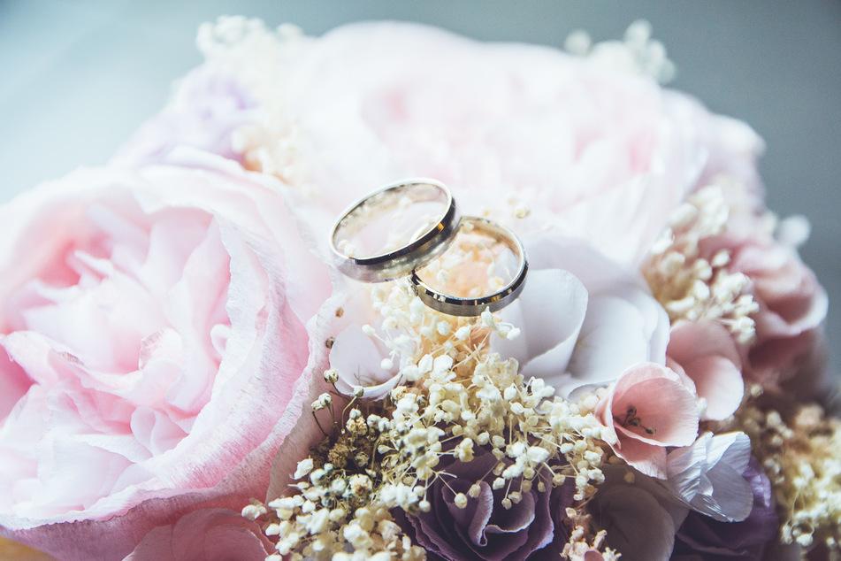 Zwei Hochzeitsringe liegen auf einem Brautstrauß. (Symbolbild)