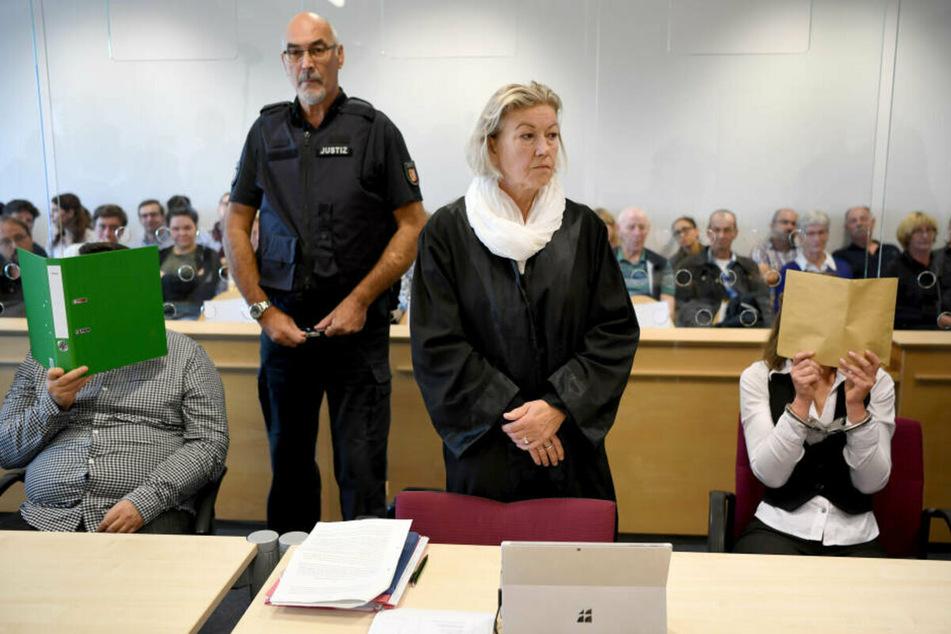 Mit verdeckten Gesichtern sitzen die Angeklagten neben ihrer Anwältin im Gerichtssaal. (Archivbild)