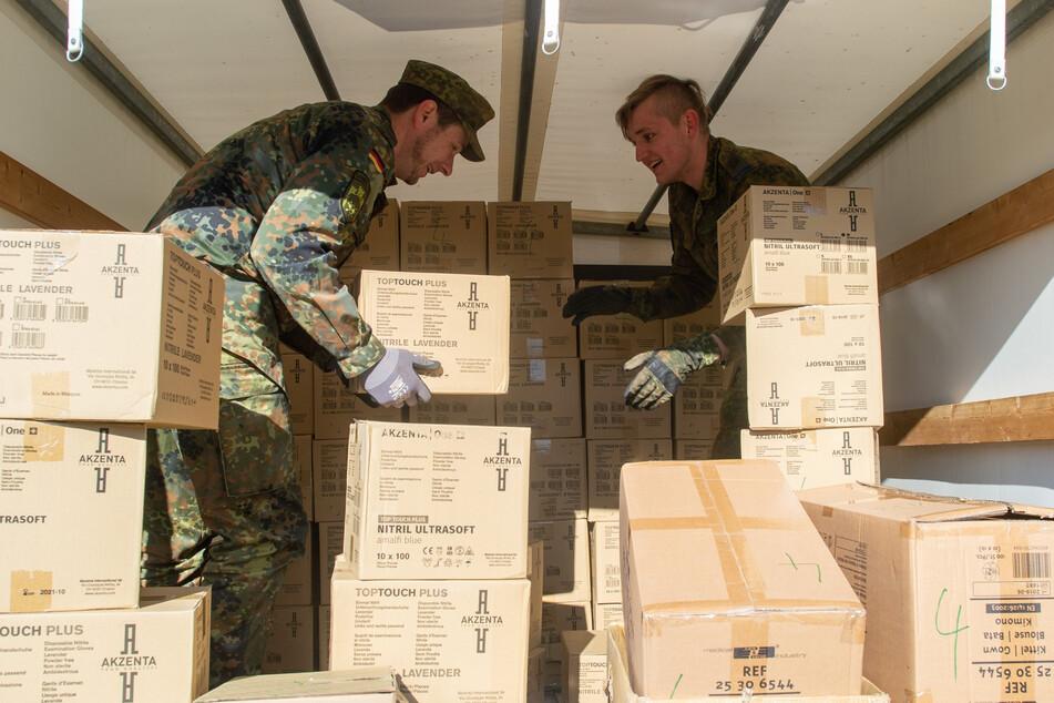 Soldaten des Logistigbattaillons 171 beladen ein Fahrzeug mit Kisten, in denen sich verschiedene Schutzmaterialien befinden.