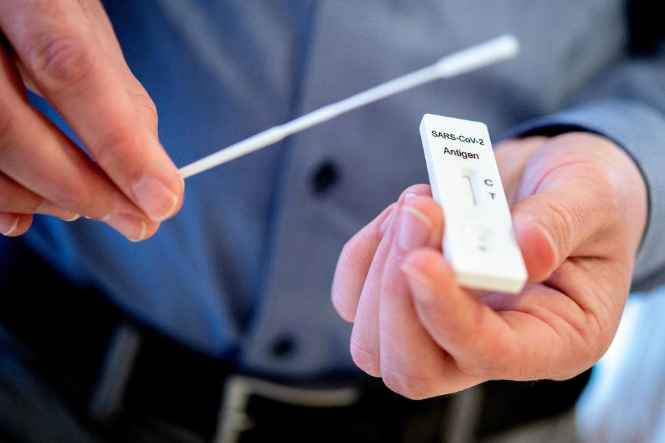 Ein Mann hält einen Schnelltest zur Erkennung des Coronavirus und ein Teststäbchen in einem Pflegeheim in den Händen.