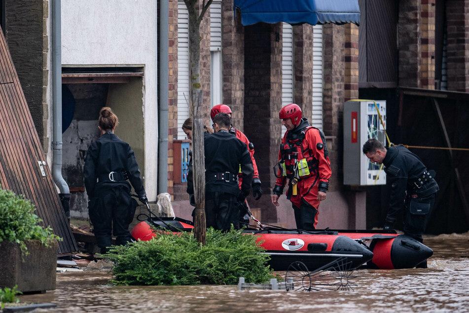 Rettungsschwimmer und Polizeitaucher sind mit Schlauchbooten in Erftstadt im Einsatz.