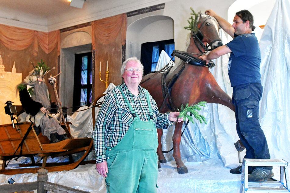 """""""Schlossherr"""" Matthias Riedel (62) reicht Robert Marutz (46) grüne Fichtenzweige für den Kopfputz des Pferdes."""