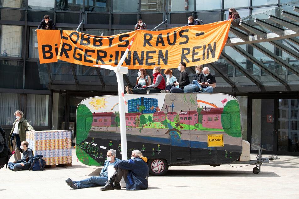 """Einige Demonstranten kletterten auf das Vordach des Landtages und entrollten ein Transparent mit der Aufschrift """"Lobbys raus - Bürger:innen rein""""."""
