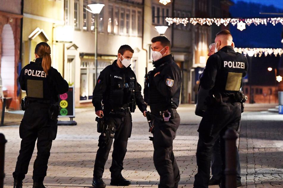 Polizisten stehen am Abend in einer Fußgängerzone und kontrollieren die neue Verordnung.