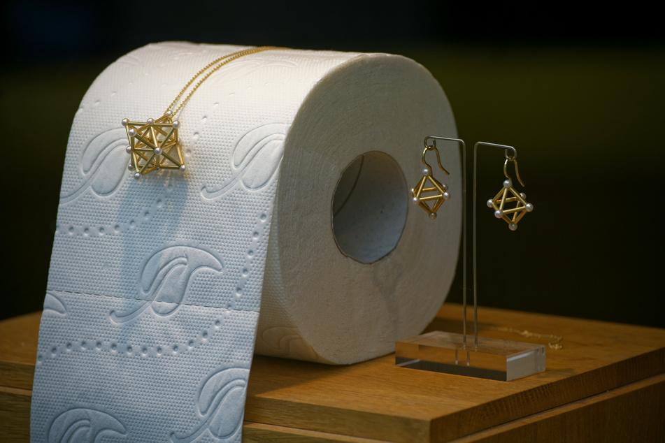 Schmuck wird im Schaufenster des Ateliers einer Goldschmiede zusammen mit Toilettenpapier zur Deko präsentiert.