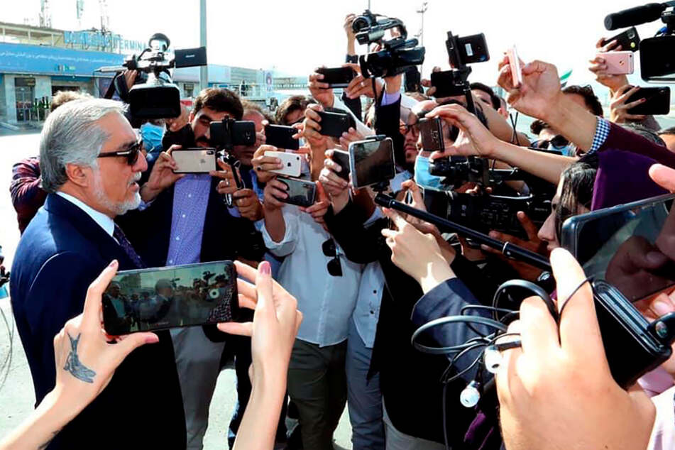 Afghanistan, Kabul: Abdullah Abdullah (l), Chairman of the High Council for National Reconciliation, talks to press representatives at Kabul International Airport.