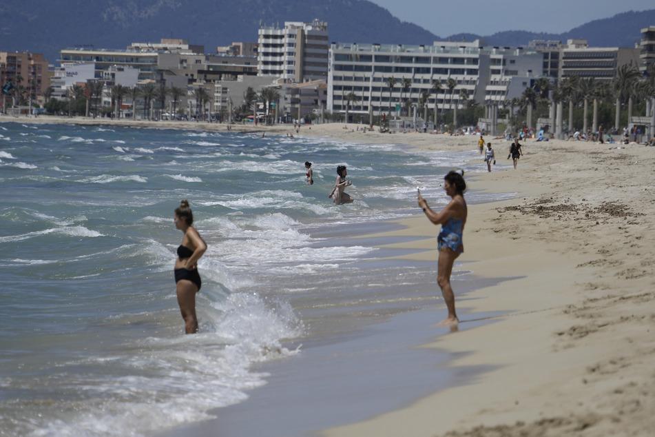 Spanien, Palma: Menschen gehen am Strand von Arenal schwimmen.