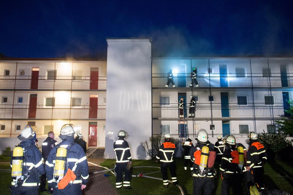 Feuerwehrleute sind bei einem Brand eines Mehrfamilienhauses im Einsatz. (Symbolbild)
