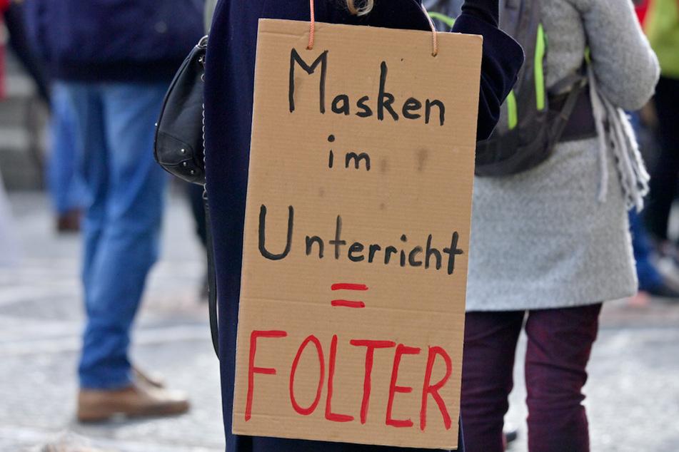 """Mit Plakaten mit der Aufschrift """"Masken im Unterricht - Folter"""" demonstrieren am Odeonsplatz mehrere hundert Menschen gegen das tragen von Mund-Nasen-Bedeckuungen in Schulen."""