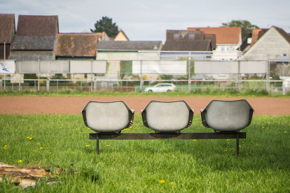 Verlassen stehen neben einem Dorfsportplatz drei Sitzplätze am Spielfeldrand. Die Amateurfußball-Saison in Bayern wurde endgültig abgebrochen.