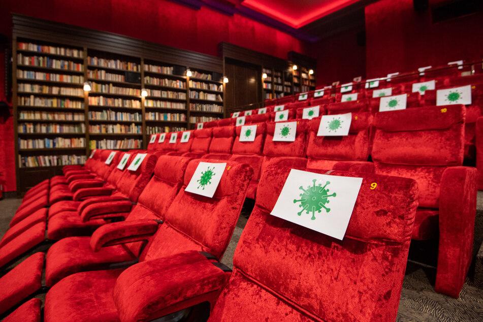 Einzelne Sitzplätze in einem Kinosaal sind mit Zetteln mit aufgedrucktem angedeuteten Virus-Symbol abgesperrt, damit Kino-Besucher einen Abstand von 1,5 Meter zueinander einhalten können.