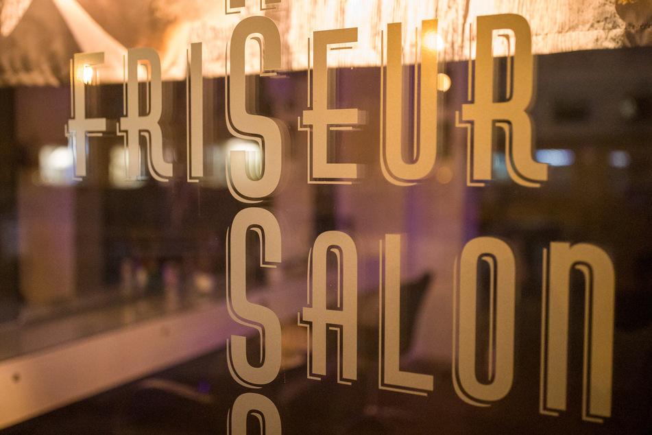 """Bayern, Nürnberg: """"Friseur Salon"""" steht auf dem beleuchteten Schaufenster eines Friseurs."""