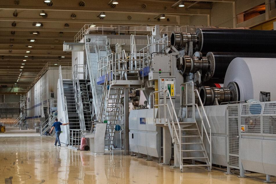 Ein Arbeiter steht an einer Papiermaschine in der Papierfabrik des Herstellers Leipa während Papierfetzen durch die Luft fliegen.