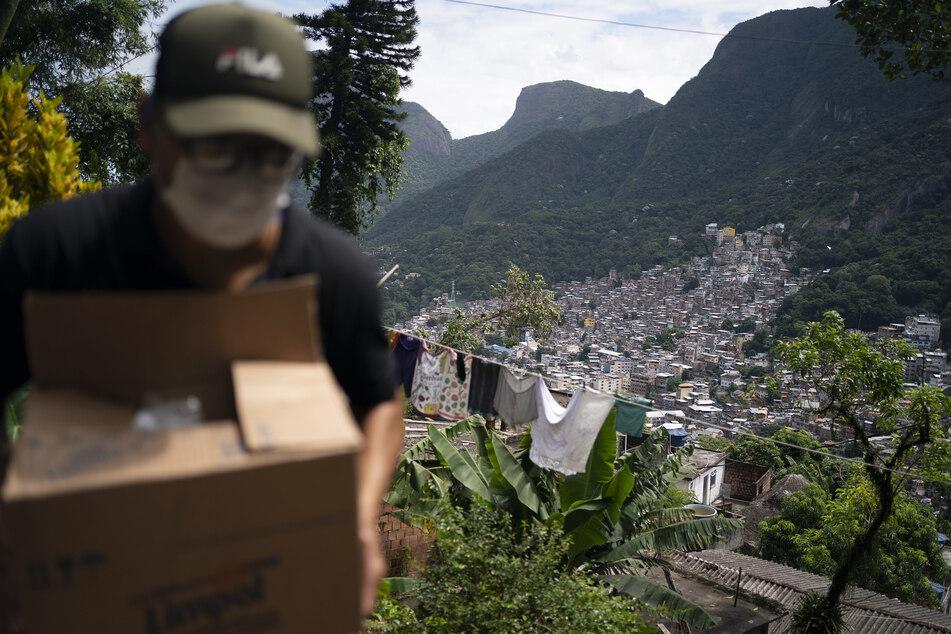 Ein Freiwilliger trägt eine Kiste mit Seife und Waschmittel, das im Kampf gegen das Coronavirus in der Rocinha-Favela verteilt werden soll.