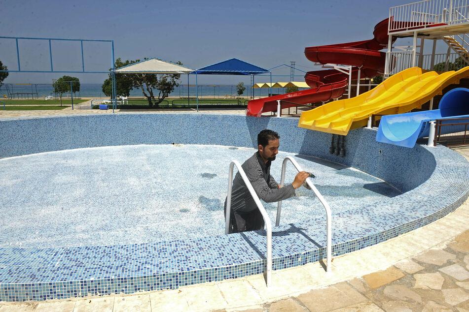 Ein Mitarbeiter einer Ferienanlage reinigt die Leiter eins Pools vor der Wiedereröffnung der Anlage in Libanon. Landesweit werden Geschäfte und Unternehmen im Rahmen der Lockerungen der Anti-Corona-Maßnahmen wieder geöffnet, um die Wirtschaft anzukurbeln.