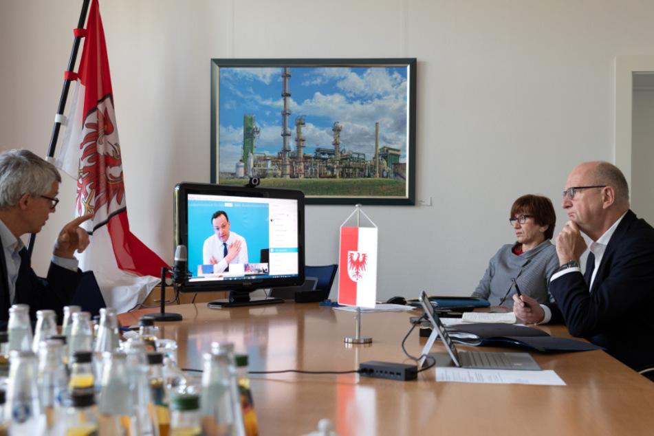 Dietmar Woidke (rechts), Ministerpräsident von Brandenburg, und Kathrin Schneider (beide SPD), Brandenburger Ministerin und Chefin der Staatskanzlei, verfolgen in der Staatskanzlei die Rede von Gesundheitsminister Jens Spahn (CDU) auf dem Monitor. Links sitzt der Brandenburger Regierungssprecher Florian Engels.