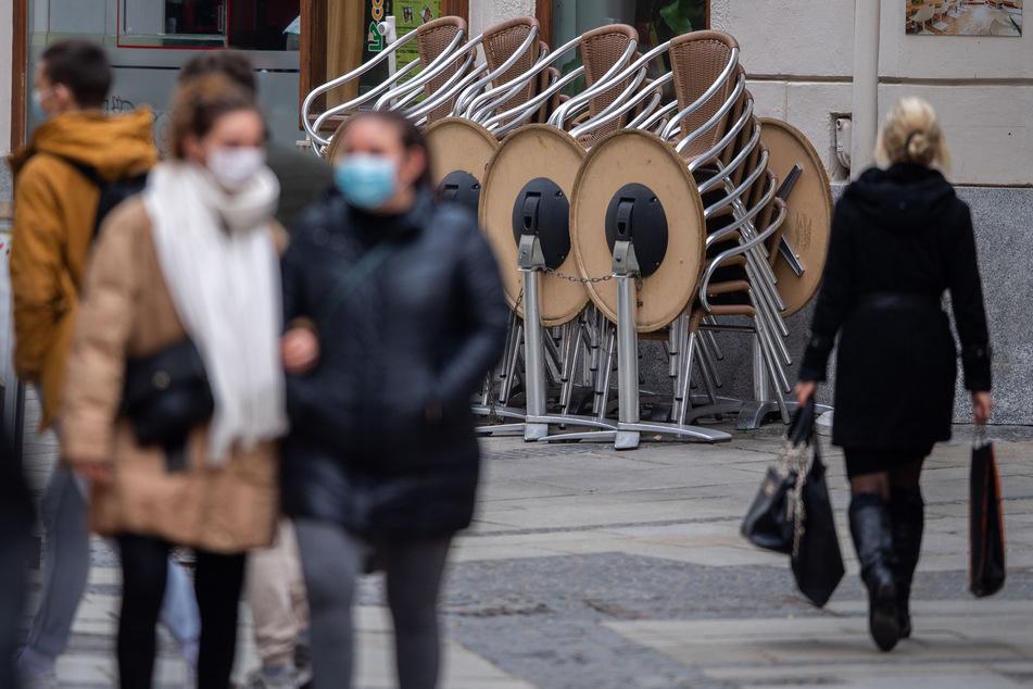 Personen gehen in der Innenstadt Passaus vor zusammengestellten Stühlen und Tischen eines Restaurants.