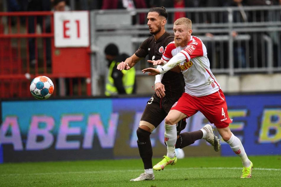 St. Paulis Leart Paqarada (links) und Regensburg Jan-Niklas Beste kämpfen um den Ball.