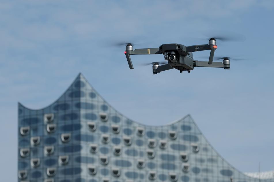Eine Drohne, die mit einer Foto/Videokamera ausgestattet ist, schwebt in der Nähe der Elbphilharmonie am Himmel.