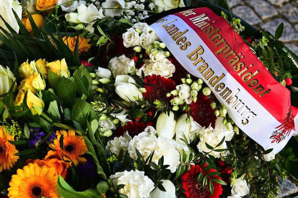 """Blumen mit einer Schleife """"Der Ministerpräsident des Landes Brandenburg"""" liegen neben anderen Blumen vor dem Eingang zur Einrichtung des diakonischen Anbieters Oberlinhaus. Die Brandenburger Landesregierung sieht nach dem gewaltsamen Tod von vier Heim-Bewohnern in Potsdam bisher keinen Zusammenhang mit der Arbeitssituation."""