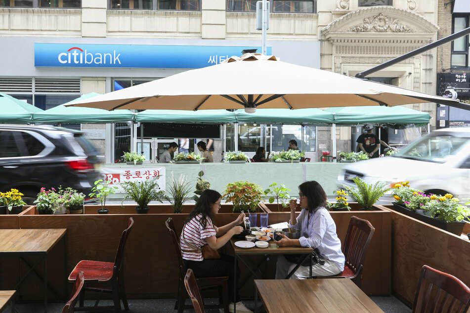 Zwei Frauen nehmen auf der Außenterrasse eines New Yorker Restaurant direkt an der Straße ihre Mahlzeit ein.