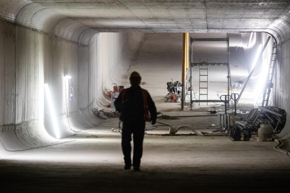 """Ein Bauarbeiter läuft durch den neuen Abwasserkanal """"Düker Nesenbach"""". Für den Bau des künftigen Stuttgarter Durchgangsbahnhofs musste einer der größten und wichtigsten Abwasserkanäle der Landeshauptstadt verlegt und neu gebaut werden."""