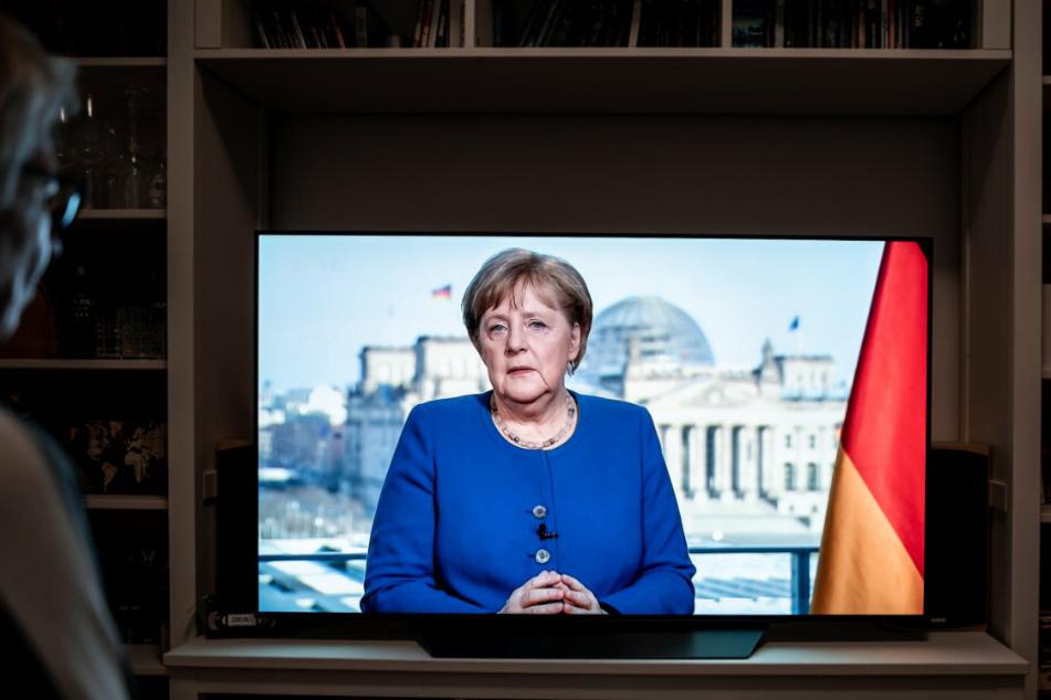 Menschen schauen die TV-Ansprache der Bundeskanzlerin Angela Merkel (CDU) in einem Wohnzimmer. (Archivbild)