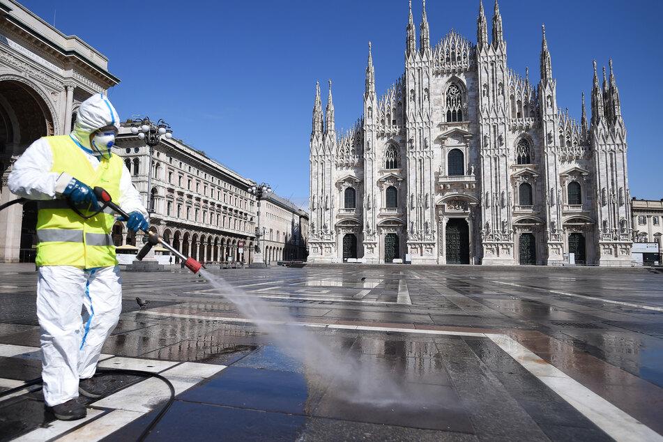 Ein Arbeiter in Schutzanzug reinigt den Boden auf der Piazza del Duomo in Mailand.