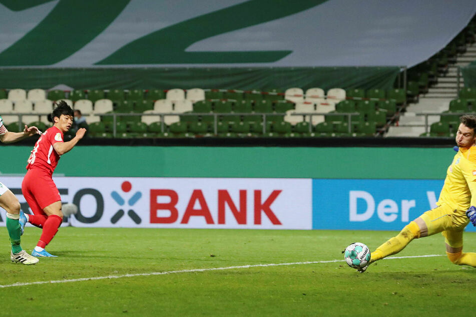 Da ist das Ding! Der eingewechselte Hee-chan Hwang (l.) schiebt den Ball an Jiri Pavlenka (r.) vorbei zum 1:0 für RB Leipzig ins Tor.