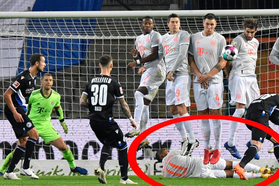 Bayerns Douglas Costa liegt quer unter der Mauer, mit dem Rücken zum Schützen und der Mauer, den Blick zu Torhüter Neuer gerichtet, die Hände vor dem Bauch verschränkt, um den Schuss zu blockieren.