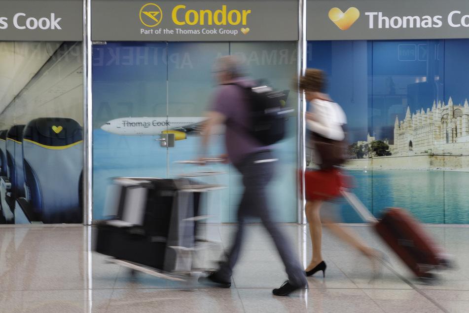 Passagiere gehen an einem Büro von Condor und Thomas Cook am Flughafen Palma de Mallorca vorbei.