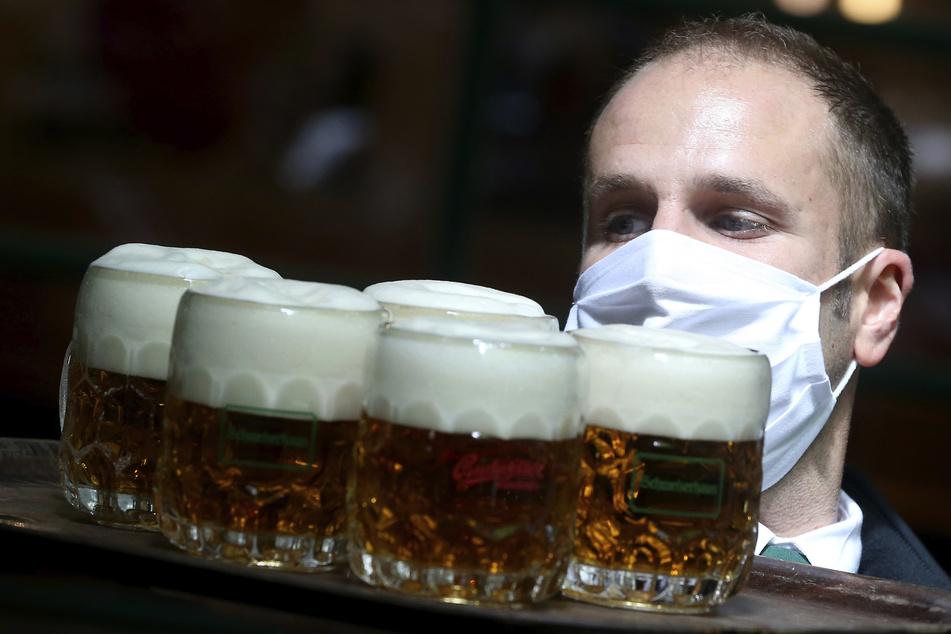 Wien: Ein Kellner mit Mundschutz trägt Bier auf einem Serviertablett durch ein Restaurant. In Österreich können ab dem 15. Mai Restaurants unter Einhaltung bestimmter Vorschriften angesichts der Corona-Pandemie wieder öffnen.